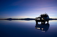 A 4x4 rests in the early AM reflection in the flooded Salar de Uyuni in Bolivia during the rainy season.