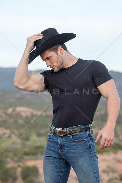 cowboy with bulging bicep outdoors