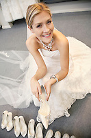 Portrait of a happy beautiful woman in wedding dress sitting with footwear in bridal store