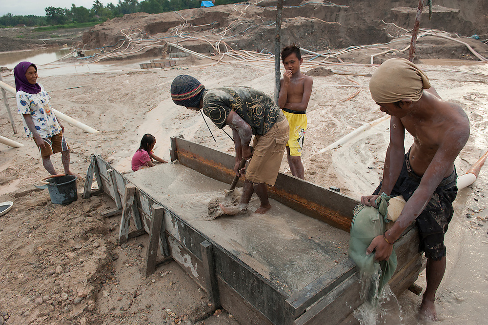 The hidden side of high tech smartphones. Miners -among them children of 10 years - sifting sand, the tin ore they find is kept in buckets.  The youngest children play beside the working adults, learning the mining skills. The entire Batako village works in the dangerous illegal mine, mere meters away from their homes. Bangka Island (Indonesia) is devastated by illegal tin mines. The demand for tin has increased due to its use in smart phones and tablets.<br /> <br /> Le côté caché du succès des smartphones. Mineurs-dont des enfants de 10 ans - tamisent du sable, le minerai d'étain trouvé est conservé dans des seaux. Les jeunes enfants jouent à côté des adultes qui travaillent, et apprennent ainsi des techniques minières. Tout le village de Batako travaille dans la mine illégale et dangereuse, à quelques mètres de leurs maisons. L'île de Bangka (Indonésie) est dévastée par des mines d'étain sauvages. La demande de l'étain a explosé à cause de son utilisation dans les smartphones et tablettes.