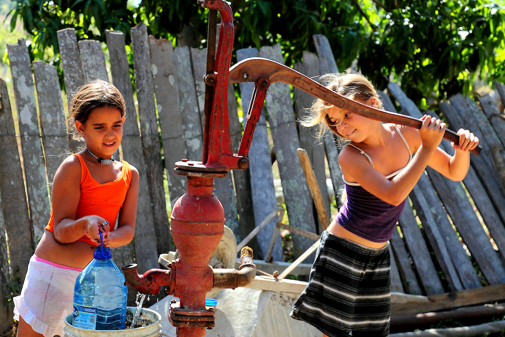 Girls pumping water at a farm in Playa La Altura, Pinar del Rio, Cuba.