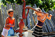 Girls pumping water at a farm in Playa La Altura, Pinar del Rio, Cuba.