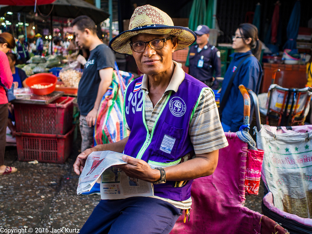 "12 JANUARY 2016 - BANGKOK, THAILAND: A porter reads a newspaper while he waits for customers Khlong Toey Market in Bangkok. Khlong Toey (also called Khlong Toei) Market is one of the largest ""wet markets"" in Thailand. The market is located in the midst of one of Bangkok's largest slum areas and close to the city's original deep water port. Thousands of people live in the neighboring slum area. Thousands more shop in the sprawling market for fresh fruits and vegetables as well meat, fish and poultry.         PHOTO BY JACK KURTZ"