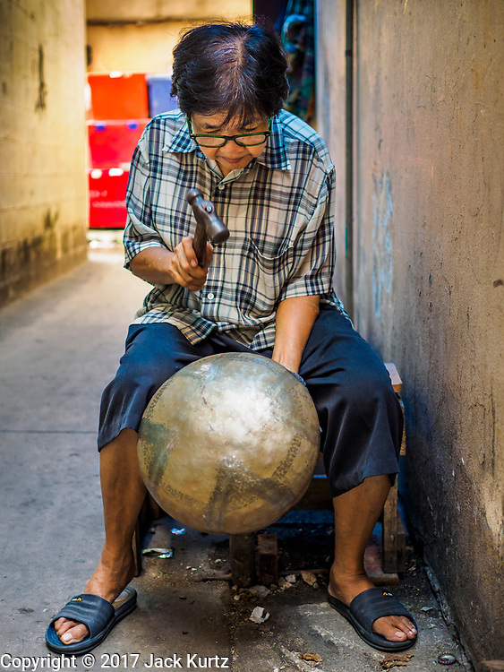 "28 MARCH 2017 - BANGKOK, THAILAND: A woman makes monks' bowls, called ""bat"" (pronounced with a long ""a"" as in baat) on Soi Baan Bat in Bangkok. The bowls are made from eight separate pieces of metal said to represent the Buddha's Eightfold Path. The Monk's Bowl Village on Soi Ban Baat in Bangkok is the only surviving one of what were originally three artisan's communities established by Thai King Rama I for the purpose of handcrafting ""baat"" the ceremonial bowls used by monks as they collect their morning alms. Most monks now use cheaper factory made bowls and the old tradition is dying out. Only six or seven families on Soi Ban Baat still make the bowls by hand. Most of the bowls are now sold to tourists who find their way to hidden alleys in old Bangkok. The small family workshops are only a part of the ""Monk's Bowl Village."" It is also a thriving residential community of narrow alleyways and sidewalks. The area is also spelled Ban Bat or Baan Bat.          PHOTO BY JACK KURTZ"
