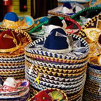 Stacks of colorful sombreros for sale at a souvenir shop in Playa del Carmen.