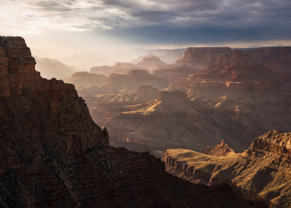 The atmosphere within the Grand Canyon is filled with light as the sun begins to set.