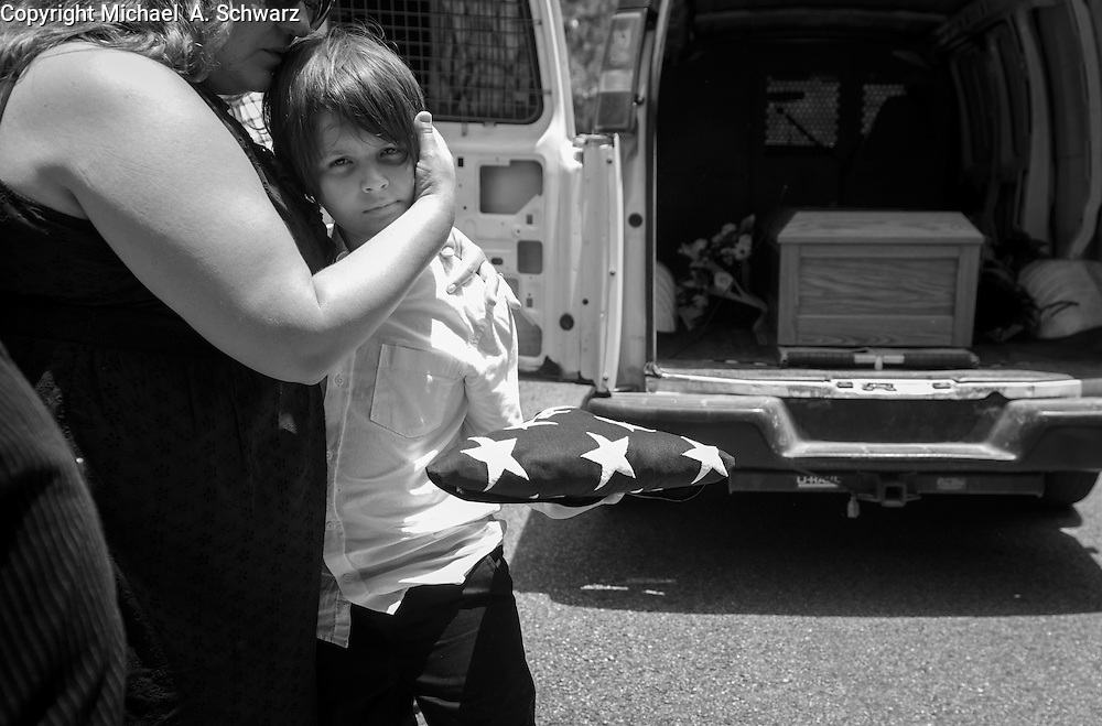 7/9/15 1:25:28 PM -- Canton, GA,  --  Skylar Akins, 11, holds the flag from his father's casket and is comforted by relative Chrissi Blackwell as Stephen Akin's casket sits in a van waiting for burial. For a story on MIlitary addictions.  --    Photo by Michael  A. Schwarz