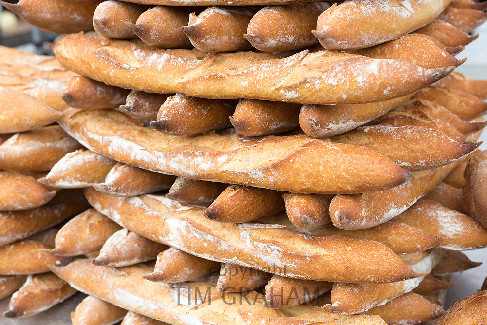 Stacked French fresh baked baguettes loaves of bread among food on sale at street market Bordeaux, France