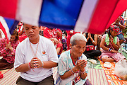 """May 12 - BANGKOK, THAILAND: Women pray in front of the Thai flag at the Red Shirts' main stage Wednesday afternoon. The Thai government said Wednesday that time has run out for """"Red Shirt"""" protesters in Ratchaprasong and Sala Daeng intersections in Bangkok and that a crackdown could come at any time. As news of the anticipated crackdown spread, Red Shirt protesters continued with an almost festive mood at their main stage but many of the sleeping areas around the protest site appeared to be empty. No official estimates on crowd size are available.  Photo by Jack Kurtz"""