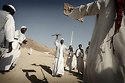 """Ababda bedouins performing """"Maggad"""" their traditional dance with swords in Wadi El Gimal, Marsa Alam, Egypt 2010"""