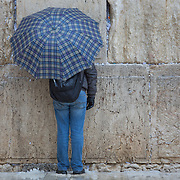 A man holding an umbrella prays at the Kotel as snow and rain fall at The Western Wall on January 7, 2015 in Jerusalem, Israel. (Photo by Elan Kawesch)