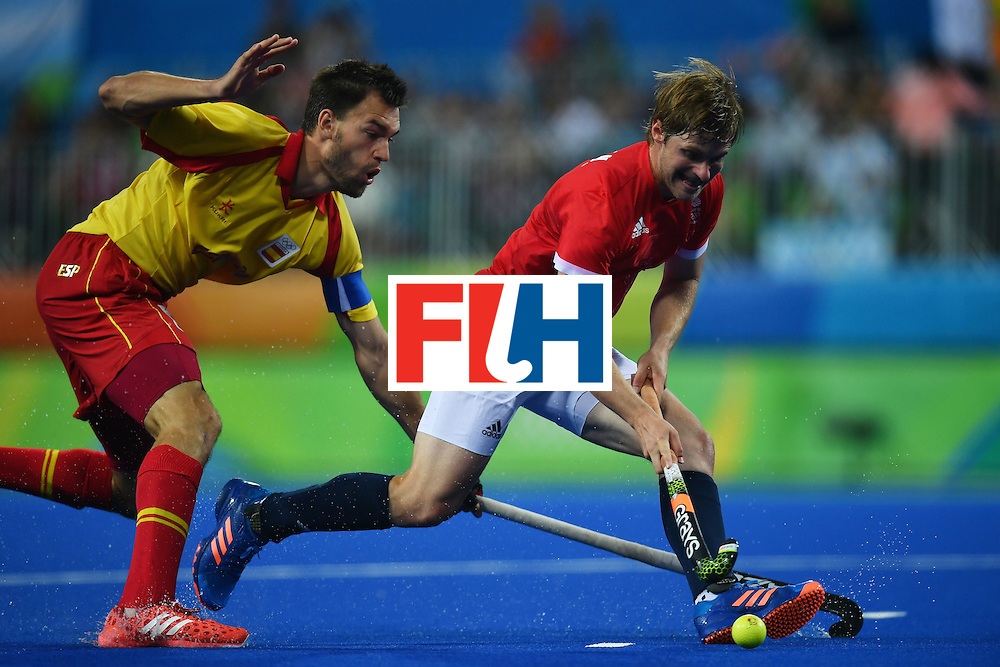 Spain's Pau Quemada (L) and Great Britain's Michael Hoare vie during the mens's field hockey Britain vs Spain match of the Rio 2016 Olympics Games at the Olympic Hockey Centre in Rio de Janeiro on August, 12 2016. / AFP / MANAN VATSYAYANA        (Photo credit should read MANAN VATSYAYANA/AFP/Getty Images)