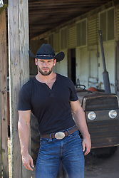 hot masculine cowboy leaning against a post on a ranch