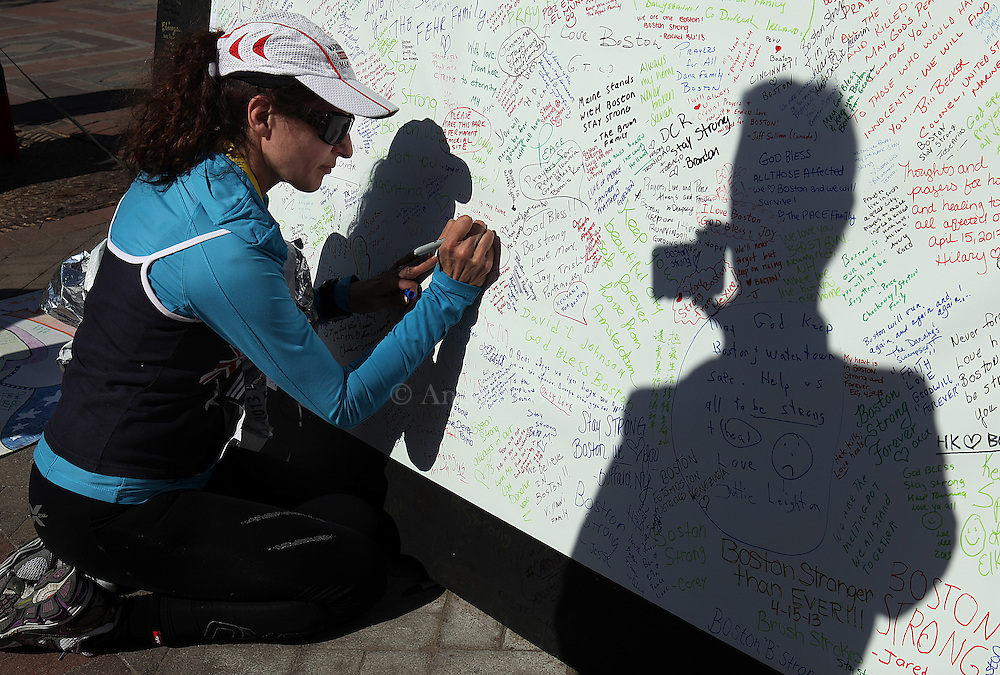 (Boston, MA - 4/29/13) Boston Marathon runner Cami Breen of Hull is videotaped by her husband, Jeff Breen, seen in shadow, while writing a mesage at the Marathon Memorial after running the last leg of the marathon route, Monday, April 29, 2013. Staff photo by Angela Rowlings.