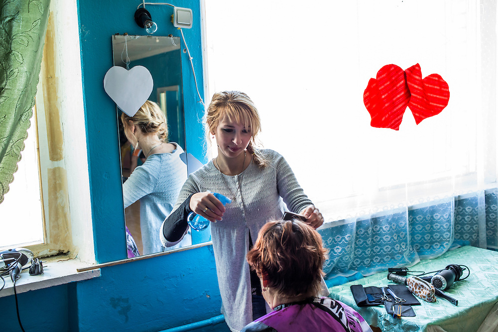 DNIPRODZERZHINSK, UKRAINE - OCTOBER 11: Dasha, who fled with her husband from Donetsk due to fighting, styles a woman's hair at the sports school where she lives with about 60 other displaced people on October 11, 2014 in Dniprodzerzhinsk, Ukraine. A professional hair stylist, she is offering free services to residents of the city as thanks for the assistance they have received. The United Nations has registered more than 360,000 people who have been forced to leave their homes due to fighting in the East, though the true number is believed to be much higher. (Photo by Brendan Hoffman/Getty Images) *** Local Caption ***