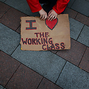 A protester holds a sign during a combined Occupy Seattle and Act Now to Stop War and End Racism (ANSWER) protest at Westlake Park on Friday, October 7, 2011. Hundreds of people gathered for the two coinciding protests. (Joshua Trujillo, seattlepi.com)