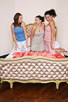 Teenage Girls at Slumber Party kneeling on funky bed