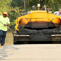 Adam Robison | BUY AT PHOTOS.DJOURNAL.COM<br /> Martin Starks, a Lee County employee, and John Robbins, job foreman, re-pave the walking track at Saltillo City Park on Monday.