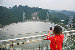 PINGTANG, Sept. 7, 2016 (Xinhua) -- A woman takes photos of the Five-hundred-meter Aperture Spherical Telescope (FAST) in Pingtang County, southwest China's Guizhou Province, Sept. 7, 2016. The FAST, world's largest radio telescope, is expected to be put into operation at the end of September. (Xinhua/Liu Xu) (wyl) (Credit Image: © Li Xu/Xinhua via ZUMA Wire)