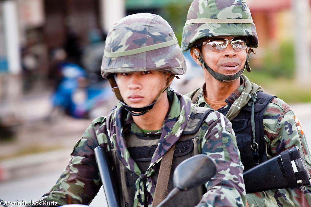 """25 SEPTEMBER 2009 -- PATTANI, THAILAND: Thai soldiers on patrol in Pattani, Thailand. The Thai army uses motorcycles to navigate the narrow streets and alleys of the cities in the south. Thailand's three southern most provinces; Yala, Pattani and Narathiwat are often called """"restive"""" and a decades long Muslim insurgency has gained traction recently. Nearly 4,000 people have been killed since 2004. The three southern provinces are under emergency control and there are more than 60,000 Thai military, police and paramilitary militia forces trying to keep the peace battling insurgents who favor car bombs and assassination.  PHOTO BY JACK KURTZ"""