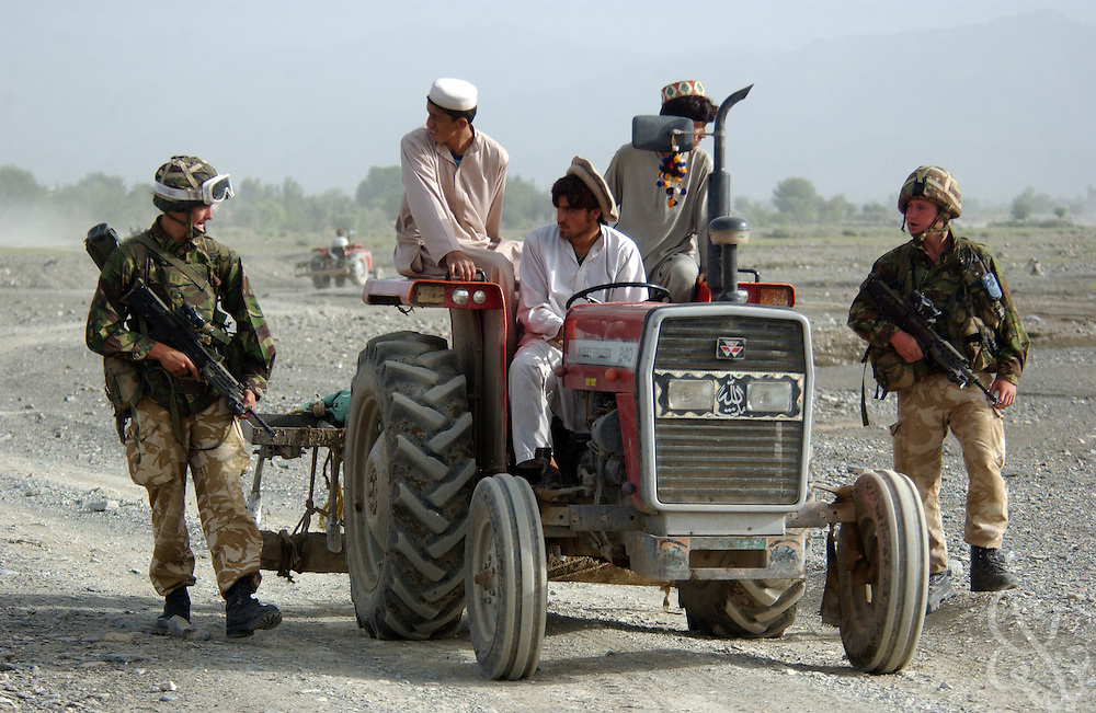 "British Royal Marine 45 Commandos stop a local Afghan man on a tractor during an ""eagle vehicle check point"" (VCP) mission for Operation Buzzard July 8, 2002 in southeastern Afghanistan. During VCPs, small groups of marines are dropped quickly by helicopters to search random vehicles on dirt roads and trails near the Pakistan-Afghanistan border to deny al Qaeda and Taliban fighters freedom of movement across the region."