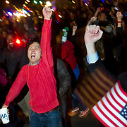 "A crowd celebrates, chanting ""four more years"" and waving four fingers in the air on U street in Washington DC after Barack Obama was announced the winner of the 2012 presidential elections."