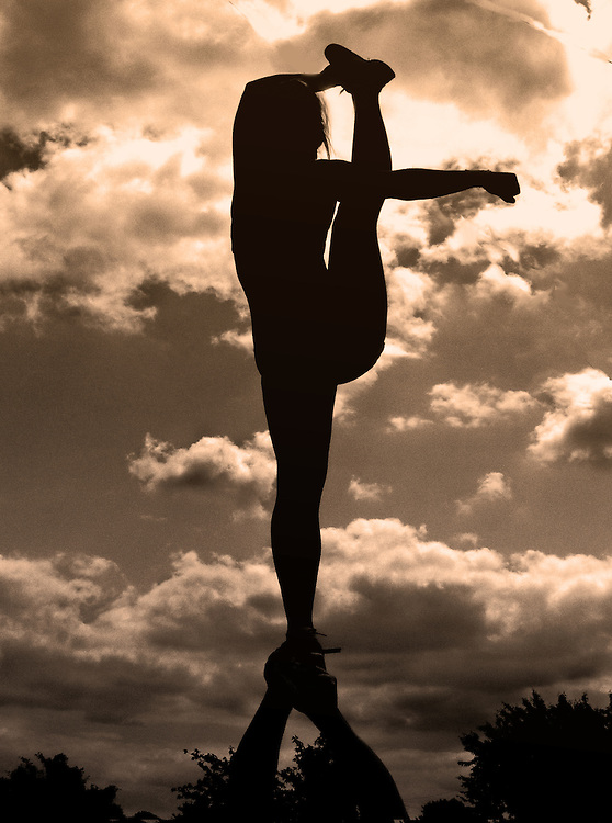 A silhouette of a cheerleading bow and arrow stretch partner stunt against a dramatic sky.