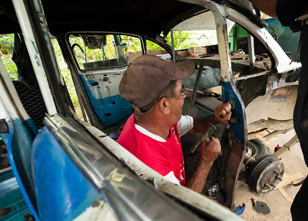 North America, Caribbean, Cuba, Vinales, man repairing car.