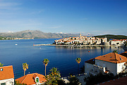 Elevated view over rooftops and palm trees of Korcula old town, looking North-East across the Peljeski Kanal, toward the Peljesac Peninsular (Croatian mainland). Island of Korcula, Croatia