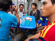04 SEPTEMBER 2013 - BANGKOK, THAILAND: Construction workers relax at a sidewalk bar and snack stand on Soi 22 Sukhumvit after their shift. The snack stand is on their walk back to the company provided dormitories they live in. The workers are building the Bhiraj Tower, a new office/retail complex under construction on Soi 35 Sukhumvit Road. It will be approximately 45 storeys when completed. The workers live in a complex of corrugated metal dorms about 1 kilometer from the construction site. They walk to and from the site every day.      PHOTO BY JACK KURTZ