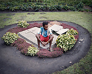 Nickolas who is HIV-positive sits next to the grave of his newborn son who died from a sudden illness 2 months ago.  Nickolas' wife is also HIV-positve.  Currently, he is not undergoing Antiretroviral Therapy (ART).