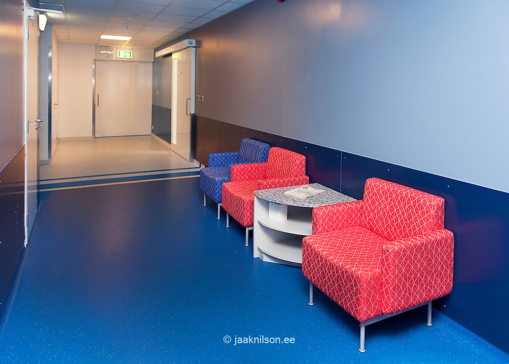Tartu university hospital  corridor and waiting area. Chairs and table. Blue floor.