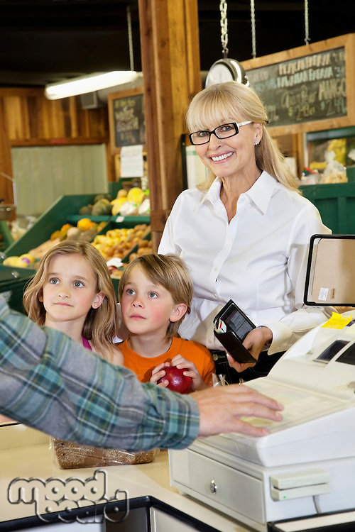 Portrait of a happy senior woman with grandchildren standing at checkout counter in farmer's market