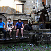 Three boys sit as penitents carry an image representing Jesus during the Maundy Thursday procession on April 17, 2014 in the northern Spanish Basque village of Segura.  PHOTO/ RAFA RIVAS