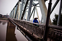 A local woman rides her bicycle across a bridge over the Red River in Yen Bai town, in northern Vietnam.