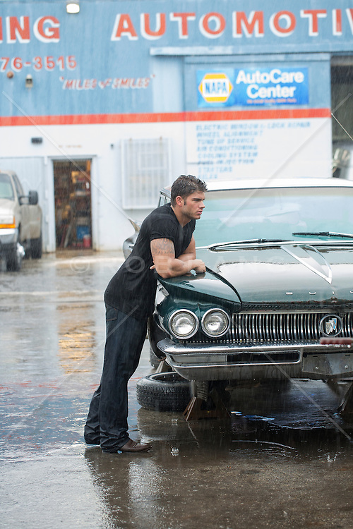 very good looking muscular auto mechanic with grease and dirt on his face leaning on a classic car in the rain