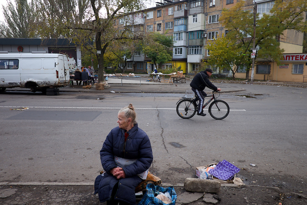 DONETSK, UKRAINE - OCTOBER 22, 2014: A local resident sells goods at the heavy bombed market area of Kievskiy district, Donetsk. Despite the constant shelling, local residents still risking their lives trying to make ends meet in one of the neighbourhoods most affected by the fighting between rebel forces and the Ukrainian army. CREDIT: Paulo Nunes dos Santos