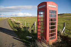 Old red telephone box standing in a country lane on Orkney; Scotland,