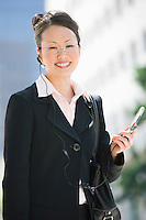Young businesswoman using mobile outdoors, portrait