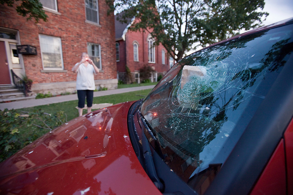 Residents photograph a brick which smashed a truck's window after a Tornado caused significant damage to the downtown core of Goderich Ontario, Sunday, August 21, 2011.<br /> THE CANADIAN PRESS/ Geoff Robins