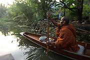 Monks on boats travel small klongs or canals collecting alms in the early morning.