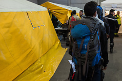 October 25, 2016 - Calais, France - A migrant with a backpack stands in the registration center at the Calais Jungle in the hall from where they will be distributed to the buses  in Calais, France, on 25 October 2016. Up to the evening, about 4,000 migrants from the Refugee camp on the coast at the English Channel were distributed to several regions in France. The police have begun to tear down the huts and tents in the camp. (Credit Image: © Markus Heine/NurPhoto via ZUMA Press)