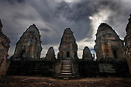 The East Mebon at Angkor Archaeological Park is a temple with five towers arranged like the numbers on a die atop a base with three tiers. The whole is surrounded by three enclosures. The towers represent the five peaks of the mythical Mount Meru.The temples of Angkor, built by the Khmer civilization between 802 and 1220 AD, represent one of humankind's most astonishing and enduring architectural achievements. From Angkor the Khmer kings ruled over a vast domain that reached from Vietnam to China to the Bay of Bengal. With more than 100 stone temples in all they are the surviving remains of a grand religious, social and administrative metropolis. whose other buildings - palaces, public buildings, and houses - were built of wood and are long since decayed and gone.