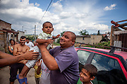 An inhabitant of the Roma settlement in Ostrovany is getting ready for a photograph with his son.