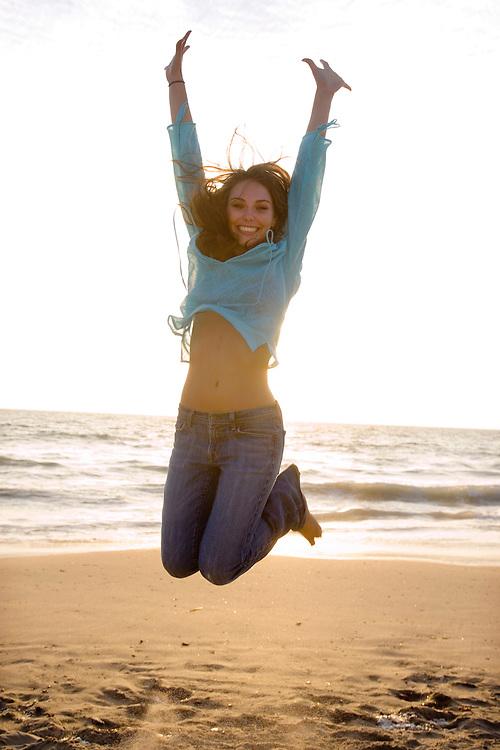 Happy Girl Leah jumps for joy at a southern California beach ay dsuk