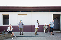 ROME, ITALY - 26 AUGUST 2016: After dinner, homeless men stand outside the dormitory of Casa Serena, a prefabricated house for homeless men in Rome, Italy, on August 26th 2016.<br /> <br /> Casa Serena, inaugurated in 1993, hosts approximately 70 men, 50 years or above, of any nationality, religion, colour. <br /> <br /> The Missionaries of Charity-Contemplative is a diocesan religious Institute composed of Brothers and priests with equal rights and obligations, founded by Blessed Teresa of Calcutta with Fr. Sebastian Vazhakala in 1979. The members take public vows of Chastity, Poverty, Obedience and free service to the poor.<br /> <br /> Mother Teresa, also known as Blessed Teresa of Calcutta, was an Albanian Roman Catholic nun and missionary. She founded the Missionaries of Charity, a Roman Catholic religious congregation, whose members must adhere to the vows of chastity, poverty, and obedience, as well as the vow to give wholehearted free service to the poorest of the poor. Shortly after she died in 1997, Pope John Paul II waived the usual five-year waiting period and allowed the opening of the process to declare her sainthood. She was beatified in 2003. A second miracle was credited to her intercession by Pope Francis, in December 2015, paving the way for her to be recognised as a saint by the Roman Catholic Church. Her canonisation is scheduled for September 4th 2016, a day before the 19th anniversary of her death.