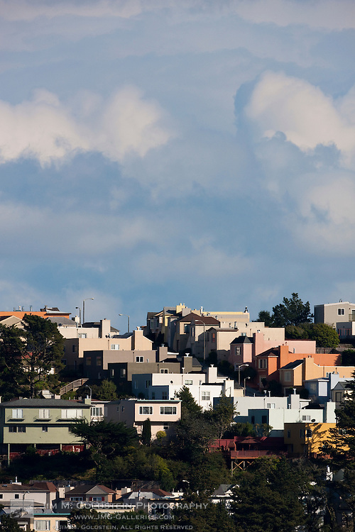 Twin Peaks homes rising up the steam mountainside to a cloudy sky above. San Francisco, California