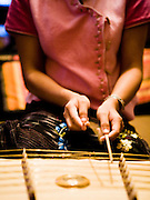 Performer playing the Ja Kae, Thai zither, at Anantara Golden Triangle resort.