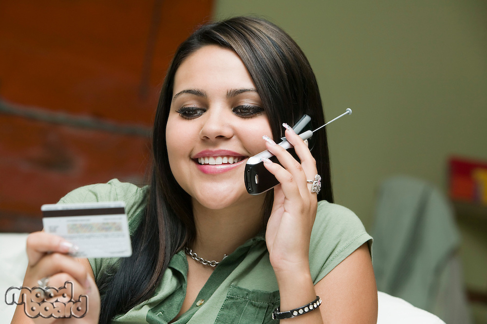 Woman Holding Credit Card Using Cell Phone