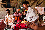 """Snake charmer Baba Prakash Nath (center, in red & white), 35, sits in a temporary camp of travelling snake charmers from Rajasthan who have pitched camp in remote Lodha Basti, Manana village, Samalkha town, Haryana, India on 15th June 2012. """"The government banned our trade but didn't give us any alternative options of livelihood,"""" says Baba Prakash Nath. India's traditional snake charmer communities suffer from a loss of livelihood because of stringent wildlife laws and  are forced to resort to begging or working as daily wage labourers. A new program to encourage the snake charmer's children to attend school is underway, to keep them from becoming daily-wage child labourers or joining their parents in scavenging and begging in cities. Photo by Suzanne Lee for The National"""